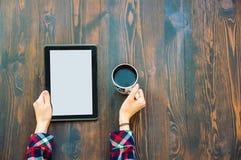 H?nder som rymmer en minnestavla och en kopp kaffe royaltyfri fotografi