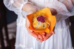 Händer som rymmer en muffin royaltyfria foton