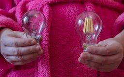 Händer som rymmer en ny ljus kula på ljusdioden och den glödande lampan Valet mellan ekonomi och effektivitet arkivfoto