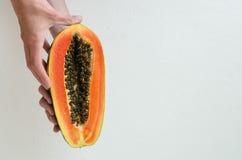 Händer som rymmer en papayaskiva Royaltyfria Bilder