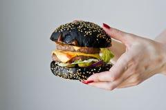 Händer som rymmer en saftig hamburgare Sidosikt, grå bakgrund, utrymme för text royaltyfri bild