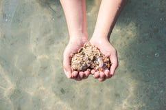 Händer som rymmer en sand i formen av hjärtan Arkivfoto