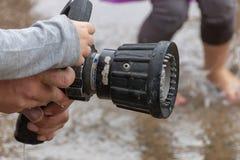 Händer som rymmer en vattenslang royaltyfria bilder
