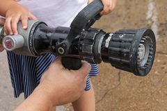 Händer som rymmer en vattenslang royaltyfri foto