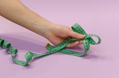 Händer som rymmer ett grönt mäta band bundet i en pilbåge på ett purpurfärgat b arkivbild