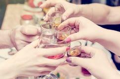 Händer som rymmer exponeringsglas med alkoholdrycker i stången arkivfoto
