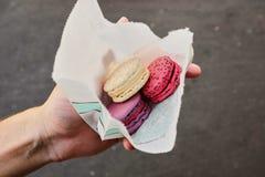 Händer som rymmer färgrika pastellfärgade kakamacarons eller makron royaltyfria foton