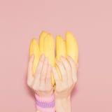 Händer som rymmer gruppen av bananer Mode vaniljstilminimalis arkivfoton