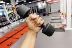 Händer som rymmer hantlar i sportklubba arkivfoton