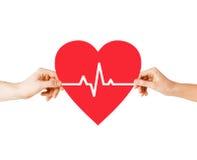 Händer som rymmer hjärta med ecglinjen Arkivbild