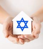Händer som rymmer huset med stjärnan av david Arkivfoto