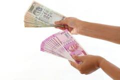 Händer som rymmer indiern 2000 och 100 rupieanmärkningar Royaltyfria Bilder