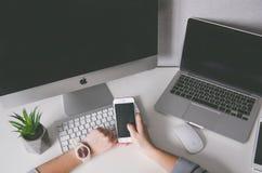 Händer som rymmer iphone7 och olika apparater på tabellen, förlöjligar upp royaltyfri bild