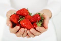 Händer som rymmer jordgubbar Arkivbilder