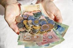 Händer som rymmer kanadensisk kassa och räkningar royaltyfri fotografi