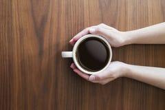 Händer som rymmer koppen för vitt kaffe och varmt espressokaffe på trä royaltyfri fotografi