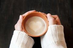 Händer som rymmer koppen kaffe med hjärta Shape Arkivfoto