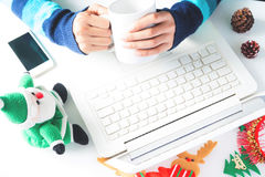 Händer som rymmer koppen kaffe och använder bärbara datorn, smartphone med julgarnering Royaltyfri Fotografi