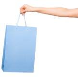 Händer som rymmer kulöra shoppingpåsar på vit bakgrund Arkivbilder