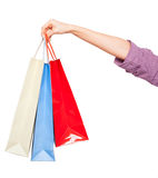 Händer som rymmer kulöra shoppingpåsar på vit bakgrund Royaltyfri Fotografi