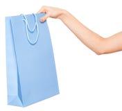 Händer som rymmer kulöra shoppingpåsar på vit bakgrund Royaltyfria Foton