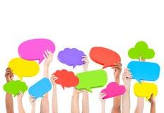 Händer som rymmer mång- kulört anförande, bubblar begrepp Arkivbild