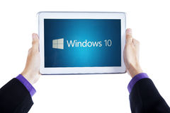 Händer som rymmer minnestavlan med fönster 10 Arkivbild