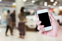 Händer som rymmer mobiltelefonen med nya bilar Fotografering för Bildbyråer