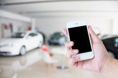 Händer som rymmer mobiltelefonen med nya bilar i visningslokal Royaltyfri Bild