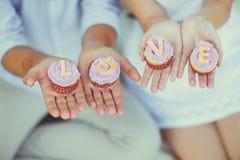 Händer som rymmer muffin med inskriften LOVE Arkivbild
