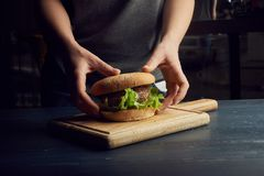 Händer som rymmer nya läckra hamburgare med den nya bullen och huggit av kött på trätabellen royaltyfria bilder