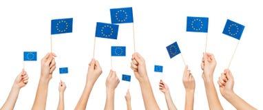 Händer som rymmer och lyfter europeiska fackliga flaggor Royaltyfri Foto