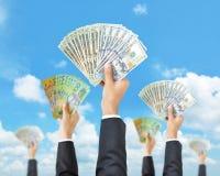 Händer som rymmer pengar i mång- valutor - lyfta för pengar som betalar Fotografering för Bildbyråer