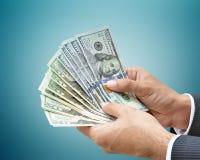 Händer som rymmer pengar - räkningar för Förenta staternadollaren (USD) - på blått Royaltyfria Bilder