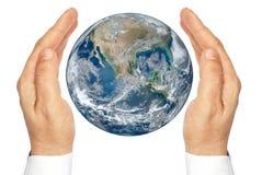Händer som rymmer planeten, jordar en kontakt isolerat på en vit bakgrund. Arkivfoto