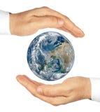 Händer som rymmer planeten, jordar en kontakt isolerat på en vit bakgrund. Arkivbild