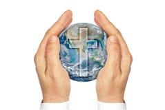 Händer som rymmer planetjorden med kristen, korsar. Arkivfoton