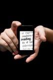 Händer som rymmer Smartphone som visar den utskrivavna ordläsningen Royaltyfri Foto