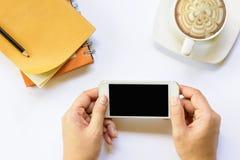Händer som rymmer smartphonen med anteckningsboken och kaffe på isolerat Zoom in Royaltyfri Bild