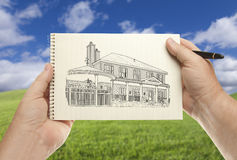 Händer som rymmer som är pappers- med huset som drar över tomt gräsfält Arkivbild