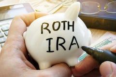 Händer som rymmer spargrisen med Roth IRA Pensionssystem royaltyfri bild