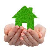 Händer som rymmer symbol för grönt hus Royaltyfria Foton