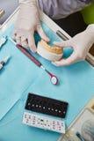 Händer som rymmer tandhänglsen över den blåa tabellen Arkivfoto