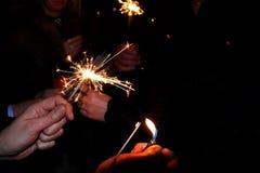 Händer som rymmer tomtebloss Folket tände tomteblossen under den chiming klockan för det nya året royaltyfri bild