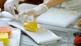Händer som sätter kakan på plattan arkivfilmer