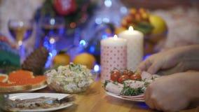Händer som sätter på en festlig tabellskinka, rullar i platta på bakgrund av stearinljus och julgranen stock video
