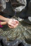 Händer som samlar vatten från springbrunnen Arkivfoto