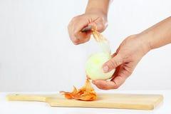 Händer som skalar den rå löken med en kniv på en skärbräda Arkivfoto