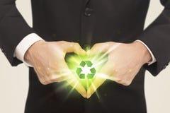 Händer som skapar en form med återvinningtecknet Royaltyfria Bilder