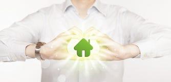 Händer som skapar en form med det gröna huset Arkivfoton